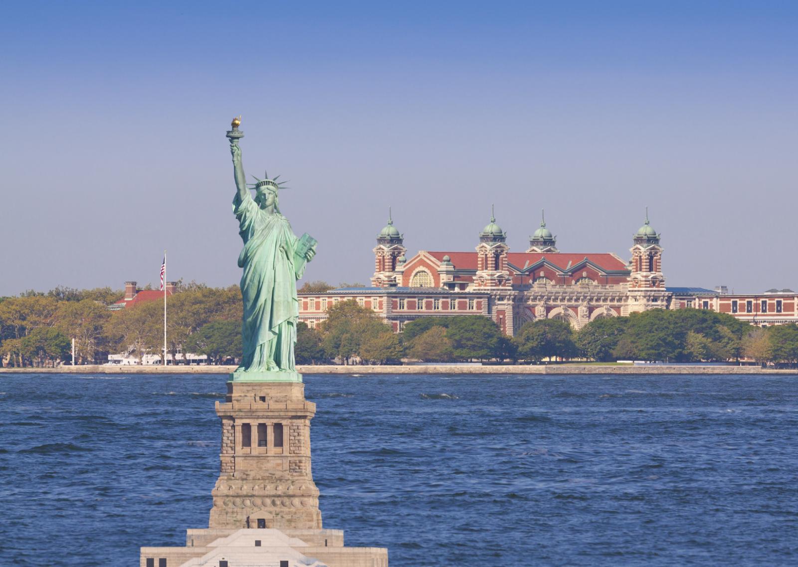 Vrijheidsbeeld met op achtergrond de aankomsthallen voor immigranten op Ellis Island